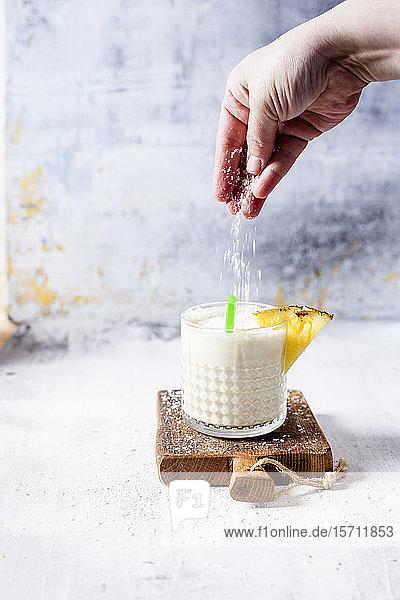 Frau streut Kokosnussflocken auf einen Ananas-Kokos-Smoothie