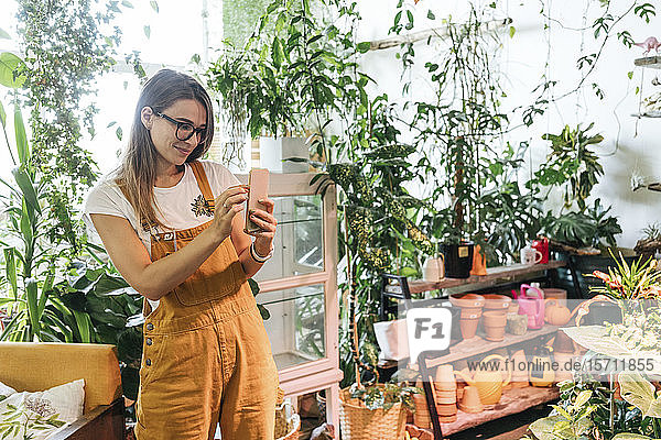 Young woman taking smartphone picture in a small gardening shop