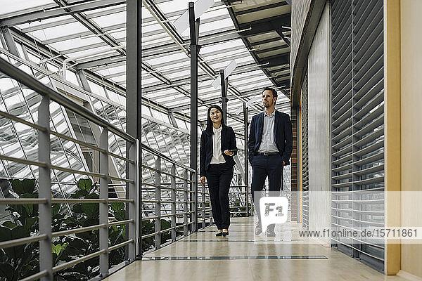 Geschäftsmann und Geschäftsfrau gehen in modernem Bürogebäude