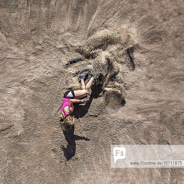 Germany  Baden-Wurttemberg  Schorndorf  Aerial view of female athlete lying on sand after long jump