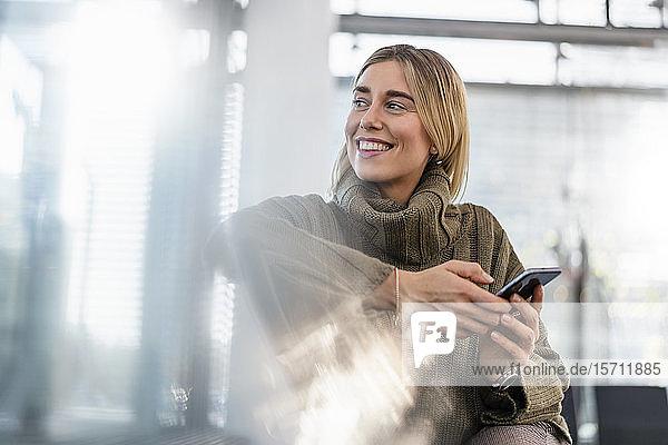 Lächelnde junge Frau mit Handy sitzt im Wartebereich und sieht sich um
