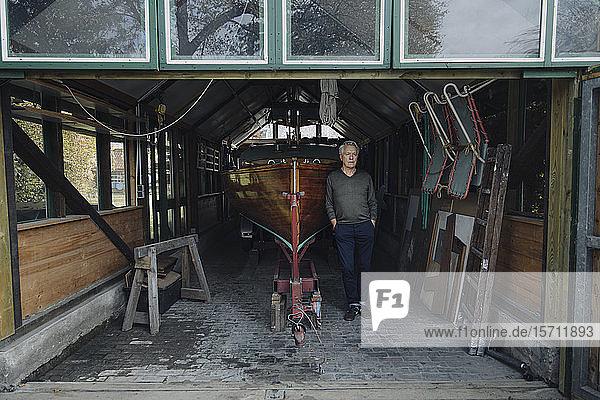 Älterer Mann steht an einem Holzboot in einem Bootshaus
