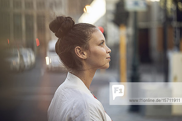 Profile view of confident young woman in the city
