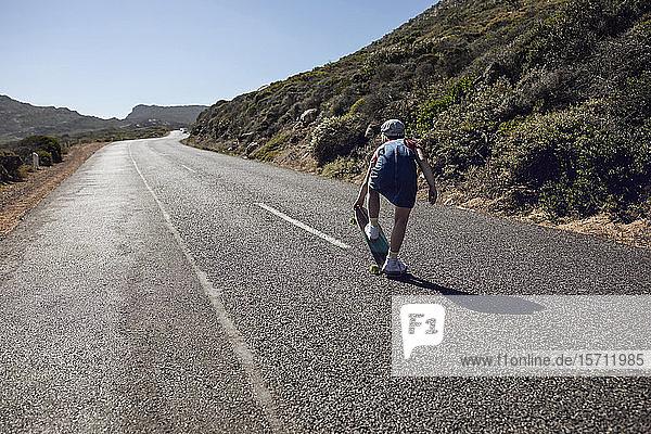 Rückenansicht eines Mädchens mit Skateboard auf der Landstraße stehend  Kapstadt  Western Cape  Südafrika