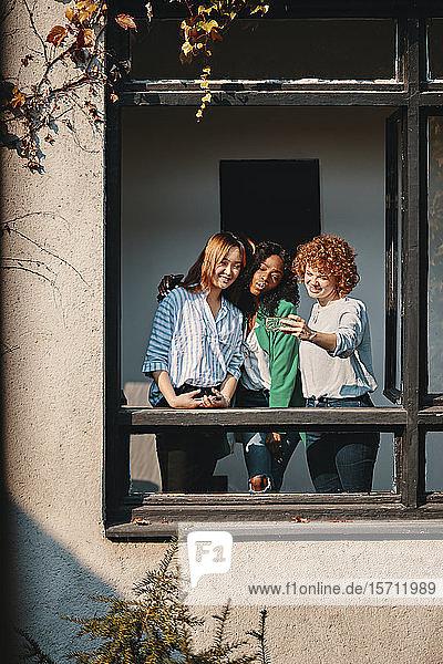 Drei Geschäftsfrauen  die am Fenster eines Bürogebäudes stehen und sich ein Selfie