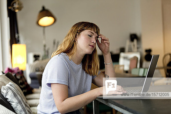 Portrait of pensive young woman sitting in a coffee shop using laptop