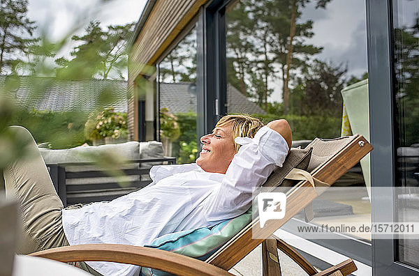 Woman relaxing in deckchair on terrace at home