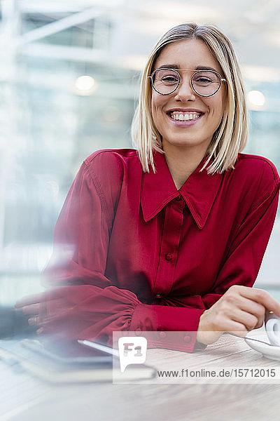 Porträt einer glücklichen jungen Geschäftsfrau in einem Cafe