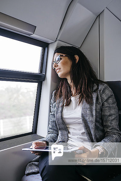 Brunette woman while traveling by train to work  with a tablet in her hands