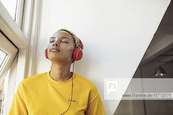 Junge Frau sitzt zu Hause am Fenster und hört Musik