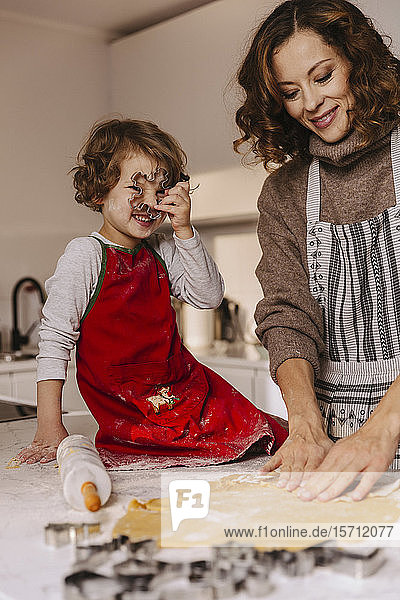 Mother and daughter preparing Christmas cookies in kitchen