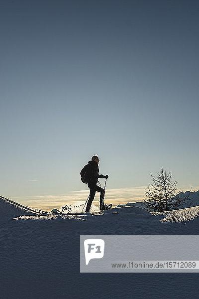 Frau wandert mit Schneeschuhen im Neuschnee in den Bergen bei Sonnenuntergang  Valmalenco  Italien
