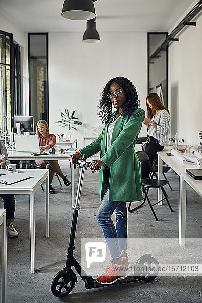 Portrait of a businesswoman with kick scooter in office