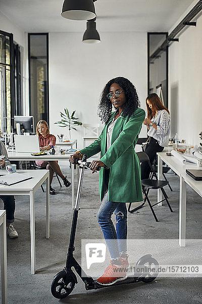 Porträt einer Geschäftsfrau mit Kickroller im Amt