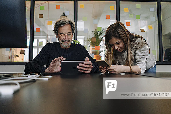Casual senior buisinessman and girl using tablet and smartphone in office