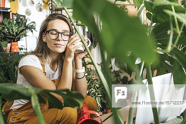 Young woman having a coffee break in a small gardening shop