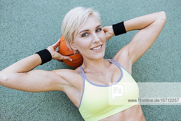 Blonde Frau auf Basketball liegend
