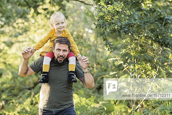 Reifer Mann spielt mit seiner kleinen Tochter in der Natur