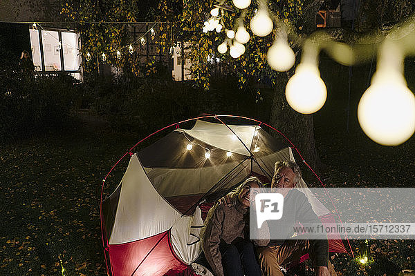 Senior couple camping in garden of their home at night