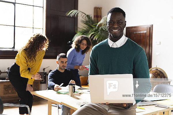 Porträt eines lächelnden Mannes im Büro mit Laptop und Kollegen im Hintergrund