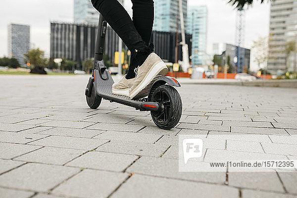 Junge Geschäftsfrau mit E-Scooter in der Stadt