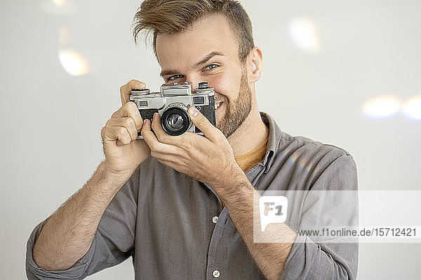 Portrait of smiling man taking picture with an old-fashioned camera