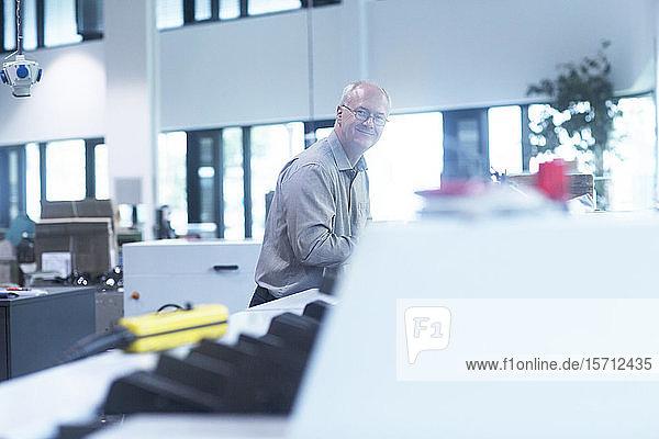 Manager arbeitet in Druckerei und schaut in die Kamera