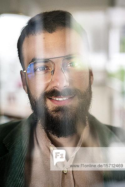 Porträt eines jungen bärtigen Mannes hinter Glasscheibe