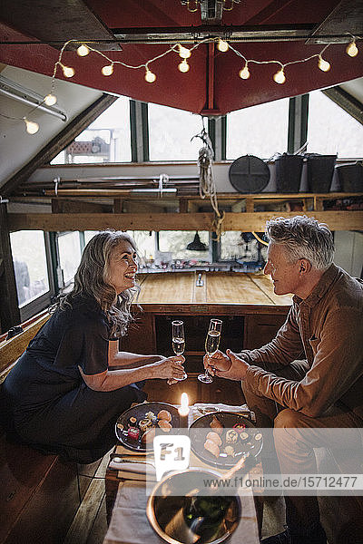 Senior couple having a candlelight dinner on a boat in boathouse