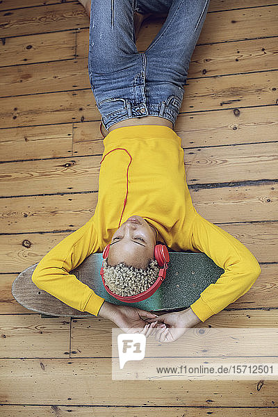 Junge Frau liegt zu Hause auf dem Skateboard auf dem Boden und hört Musik