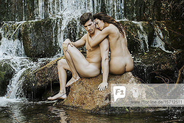 Nude young couple in front of a waterfall