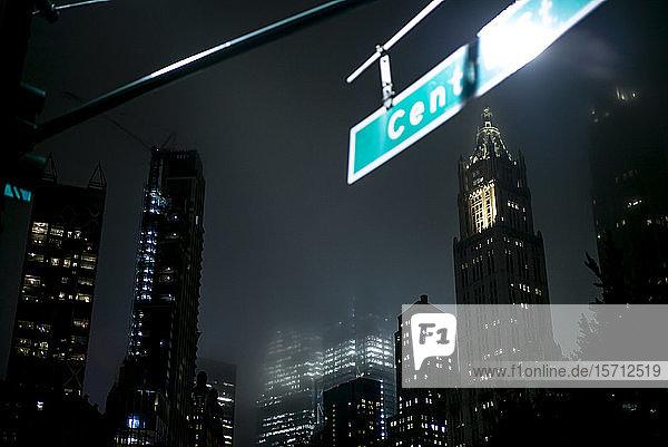 USA  New York  New York City  Straßennamensschild  das nachts an beleuchteten Wolkenkratzern hängt