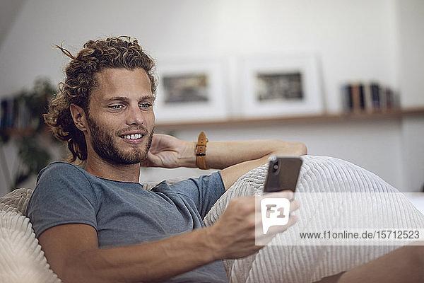 Lächelnder junger Mann entspannt sich im Sitzsack zu Hause am Handy