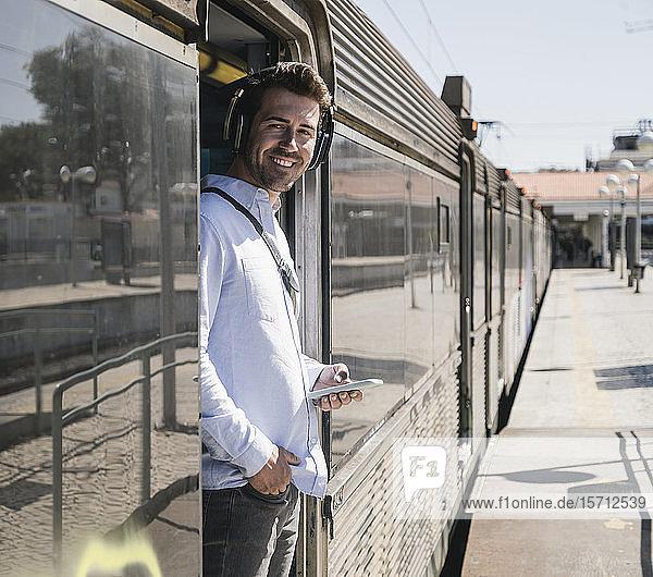 Lächelnder junger Mann mit Kopfhörern und Smartphone steht in der Zugtür