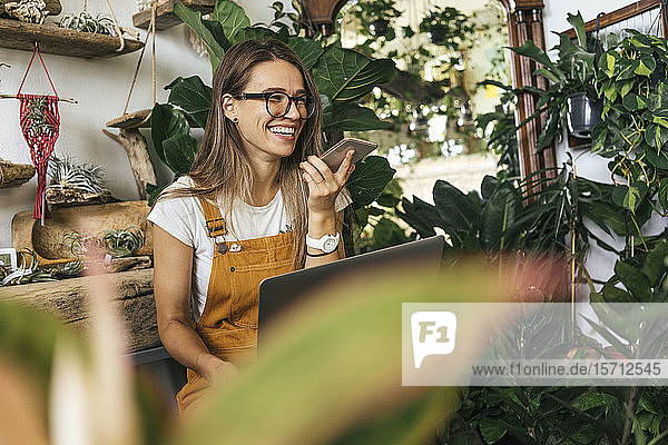 Happy young woman using smartphone in a small gardening shop