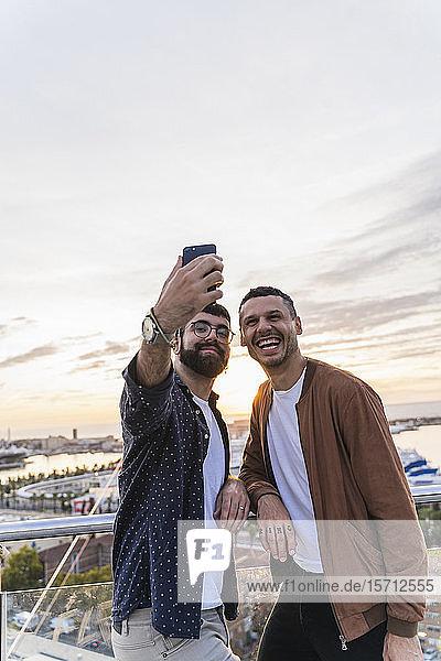 Homosexuelles Paar  das sich auf einem Aussichtspunkt über der Stadt mit Blick auf den Hafen einrichtet  Barcelona  Spanien