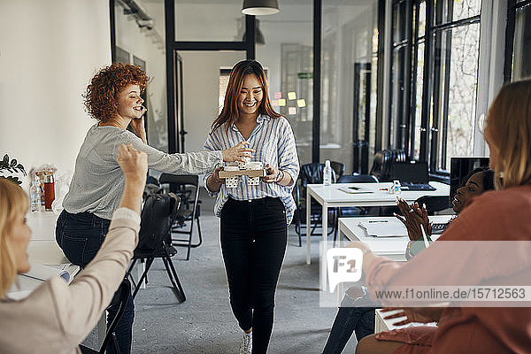 Businesswoman serving coffee to colleagues in office