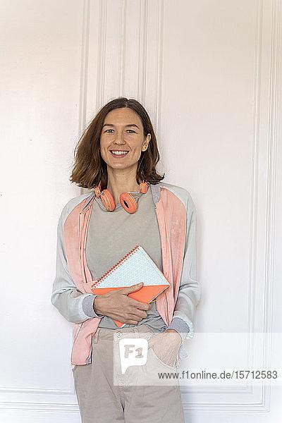 Porträt einer lächelnden Frau mit einem Notizbuch