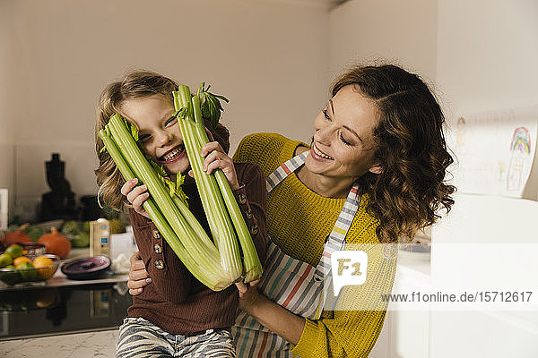 Playful girl with her mother holding celery in kitchen