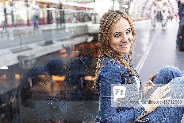 Porträt einer lächelnden Frau  die am Bahnhof wartet  Berlin  Deutschland