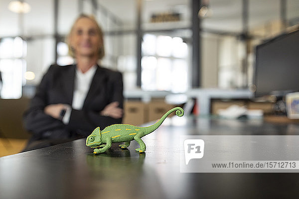 Mature businesswoman with chameleon figurine on desk in office