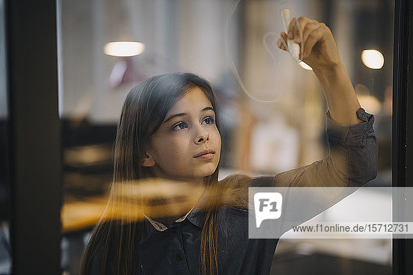 Girl drawing on glass pane in office
