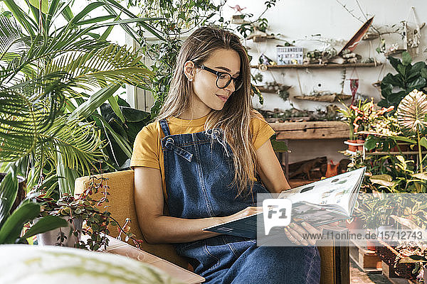 Portrait of a young woman sitting in armchair reading a book in a small gardening shop