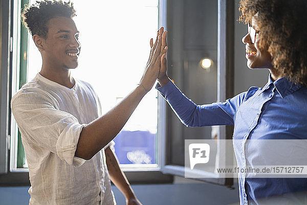 Glücklicher junger Mann high fiving mit Kollege in einem Cafe Glücklicher junger Mann high fiving mit Kollege in einem Cafe
