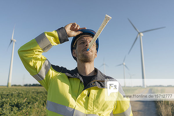 Portrait of an engineer with party blower at a wind farm