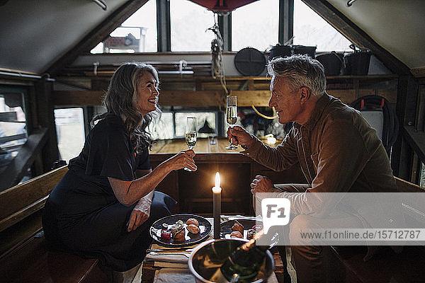 Älteres Ehepaar beim Candle-Light-Dinner auf einem Boot im Bootshaus  Champagnergläser klirrend