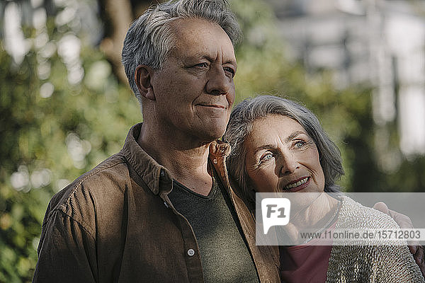 Portrait of confident senior couple in garden of their home in autumn