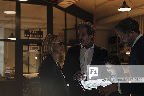 Business people and girl looking at shining construction plan on tablet in office