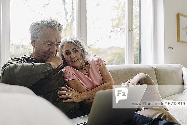 Älteres Ehepaar betrachtet Laptop auf der Couch zu Hause
