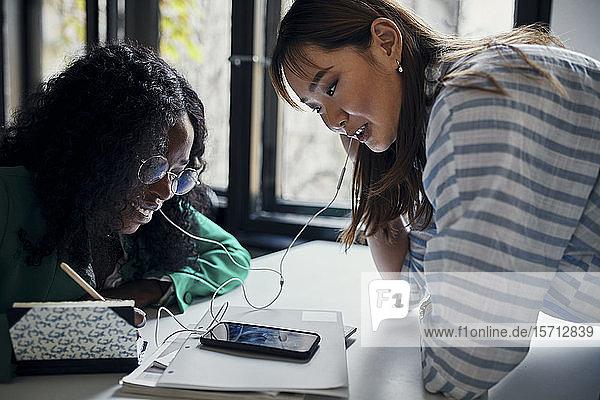 Zwei Geschäftsfrauen teilen sich Smartphone und Kopfhörer im Büro
